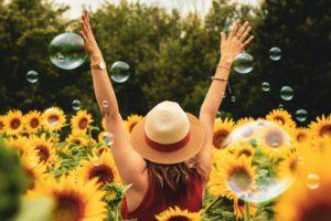 Frau inmitten von Sonnenbumen und Seifenblasen