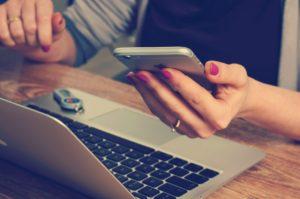 Frau hält Handy und sitzt vor dem Laptop